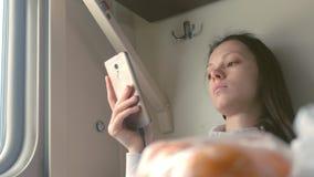 De vermoeide vrouw leest een boek die in smartphone op een lange-afstandstrein reizen stock video