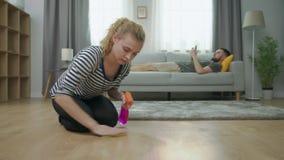 De vermoeide vrouw maakt parketvloer en haar echtgenoot liggend op bank met smartphone schoon stock footage