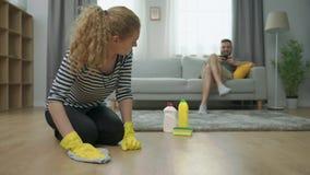 De vermoeide vrouw maakt parketvloer en haar echtgenootspel op smartphone op bank schoon stock footage