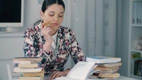 De vermoeide vrouw met een potlood treft voor examen voorbereidingen stock video
