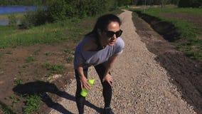 De vermoeide vrouw neemt onderbreking na het lopen stock video