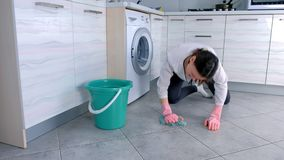 De vermoeide vrouw in roze rubberhandschoenen wast de keukenvloer met een doek Grijze tegels op de vloer stock footage
