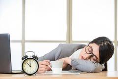 De vermoeide vrouw slaapt en houdt koffie Stock Fotografie