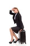 De vermoeide vrouw zit bij de zwarte koffer Royalty-vrije Stock Afbeeldingen