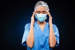 De vermoeide vrouwelijke arts in medisch masker en GLB heeft een geïsoleerde hoofdpijn Stock Foto