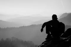 De vermoeide wandelaar met sportieve rugzak zit op rotsachtige piek en het letten op in diepe nevelige valleiblaasbalg Zonnige de stock fotografie
