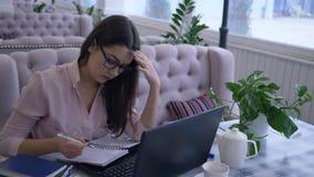 De vermoeide Werkverslaafde bedrijfsvrouw gebruikt moderne computertechnologie tijdens ver bedrijfs planning en beheer en maakt stock footage