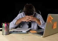 De vermoeide zakenman die het werk aan spanning lijden verspilde ongerust gemaakte bezig in bureau laat bij nacht met laptop comp stock foto's