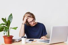 De vermoeide zakenman heeft hoofdpijn exasperately in documenten, het werk de hele dag door bij financieel verslag kijken, bereke stock afbeelding