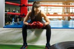 De vermoeide zitting van de meisjesatleet in de boksring de mooie vrouw houdt indient bokshandschoenen stock foto's