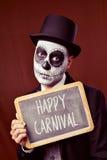 De vermomde mens toont bord met de tekst gelukkig Carnaval Stock Foto's