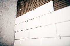 De vernieuwing, sluit omhoog details van plastiek distancer op keramische tegels en kleefstof op muren stock afbeelding