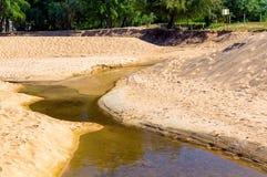 De verontreiniging van het zandstrand Zwart water in kreek op zand stock foto's