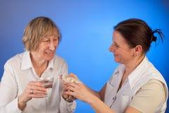 De verpleegster deelt pillen aan hogere vrouw uit stock fotografie