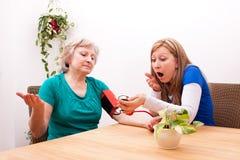 De verpleegster en de patiënt worden verrast door de bloeddruk Stock Afbeelding
