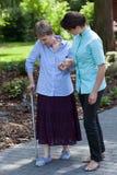 De verpleegster gaat voor een gang met de oude dame Royalty-vrije Stock Foto's