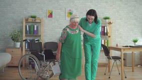 De verpleegster helpt een bejaarde uit een rolstoel krijgen stock footage