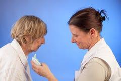 De verpleegster leest de temperatuur van hogere vrouw royalty-vrije stock afbeeldingen