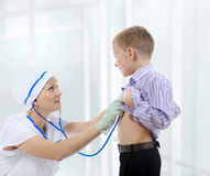 De verpleegster luistert aan een jonge patiënt Stock Foto's
