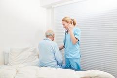 De verpleegster luistert aan patiënt met stethoscoop stock afbeelding