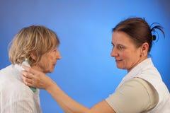 De verpleegster meet koorts van bejaarde royalty-vrije stock foto's