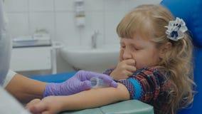 De verpleegster neemt bloedmonster van een ader in het wapen van meisje Stock Afbeelding
