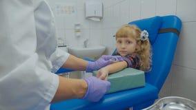 De verpleegster neemt bloedmonster van een ader in het wapen van meisje stock afbeeldingen