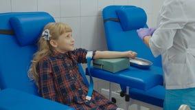 De verpleegster neemt bloedmonster van een ader in het wapen van meisje stock fotografie