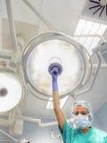 De verpleegster plaatst chirurgische lamp op de werkende lijst Royalty-vrije Stock Afbeeldingen