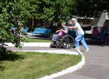De verpleegster rolt een bejaarde in een rolstoel op het grondgebied van het ziekenhuis van veteranen van oorlogen Royalty-vrije Stock Foto