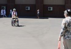 De verpleegster rolt een bejaarde in een rolstoel op het grondgebied van het ziekenhuis van veteranen van oorlogen Stock Fotografie