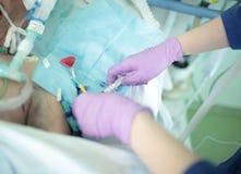 De verpleegster spuit een drug binnen in de catheter van een bejaarde patiënt in royalty-vrije stock fotografie