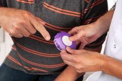 De verpleegster toont hoe te om een inhaleertoestel te gebruiken stock fotografie