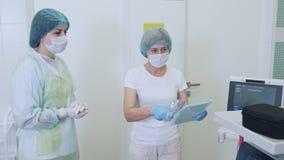 De verpleegsters in steriele kleren, maskers en handschoenen bereidt chirurgische medische dekking v??r chirurgie voor stock video