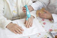 De verpleger zet de room op de hand van de oude vrouw Kosmetische behandeling en verzorging royalty-vrije stock afbeeldingen