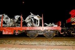 De verpletterde auto wordt weg vervoerd Echte autoneerstorting met trein De vrouwenbestuurder is dood Royalty-vrije Stock Foto