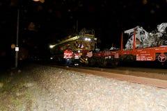 De verpletterde auto wordt weg vervoerd Echte autoneerstorting met trein De vrouwenbestuurder is dood De brandbestrijders finishe Royalty-vrije Stock Foto