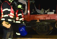 De verpletterde auto wordt weg vervoerd Echte autoneerstorting met trein De vrouwenbestuurder is dood Brandbestrijders het schoon Stock Afbeeldingen
