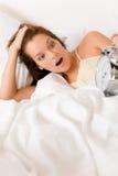 De verrassing van de slaapkamer - vrouw met wekker omhoog kielzog Royalty-vrije Stock Foto