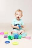 De verraste aanbiddelijke zitting van de babyjongen op de vloer en het spelen met zijn speelgoed Stock Afbeeldingen