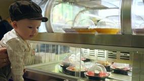 De verraste baby kijkt op showcase met verschillende sushi bij het bewegen van platen in kantine stock video