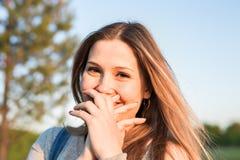 De verraste jonge vrouw met overhandigt haar mond openlucht Royalty-vrije Stock Afbeeldingen