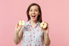 De verraste jonge vrouw in de zomer kleedt het houden van mond open greep halfs van vers rijp appelfruit op roze pastelkleur stock foto