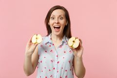 De verraste jonge vrouw in de zomer kleedt het houden van mond open greep halfs van vers rijp die appelfruit op roze pastelkleur  royalty-vrije stock fotografie