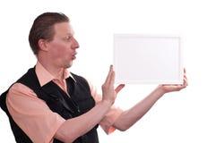De verraste mens houdt een leeg frame stock foto