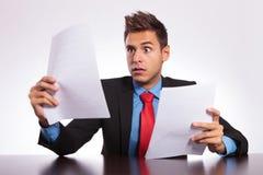 De verraste mens leest brief bij bureau Stock Foto's