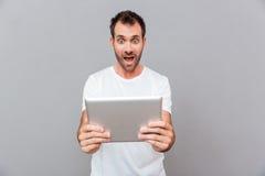 De verraste tablet van de jonge mensenholding over grijze achtergrond Royalty-vrije Stock Afbeeldingen