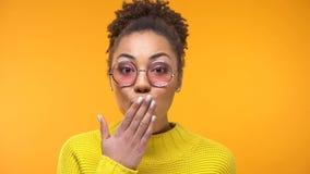 De verraste vrij vrouwelijke behandelende mondhand, stuitend nieuws, hield op met gebaar, geheim stock fotografie