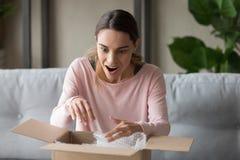 De verraste vrouw pakt kartondoos uit thuis voelt gelukkig stock afbeeldingen