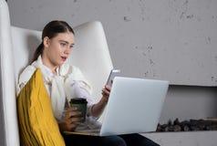 De verraste vrouwenkandidaat ontving een schokgolfbulletin op de mobiele telefoon, zittend met draagbare laptop computer en haalt stock foto